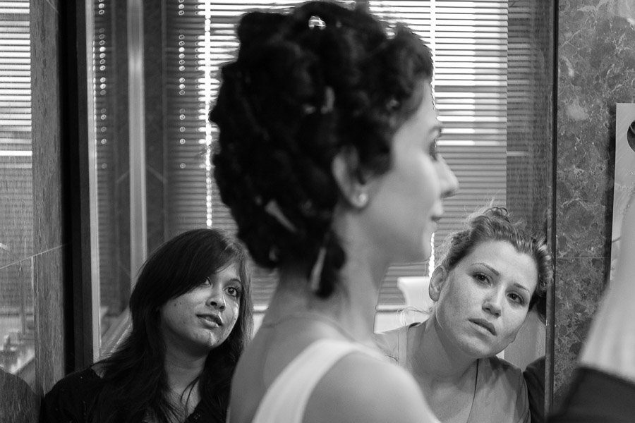 Friends of bride watching as she is getting her make up done