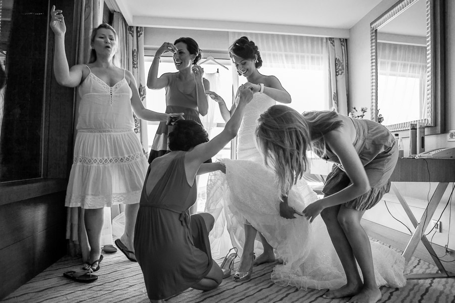 Friends helping bride putting her shoes on