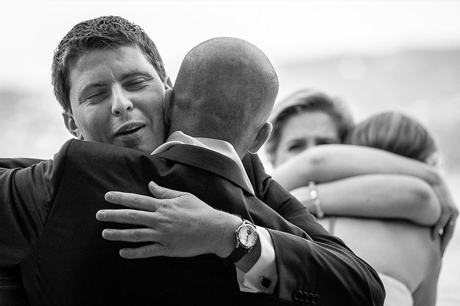 brother of bride hugs groom