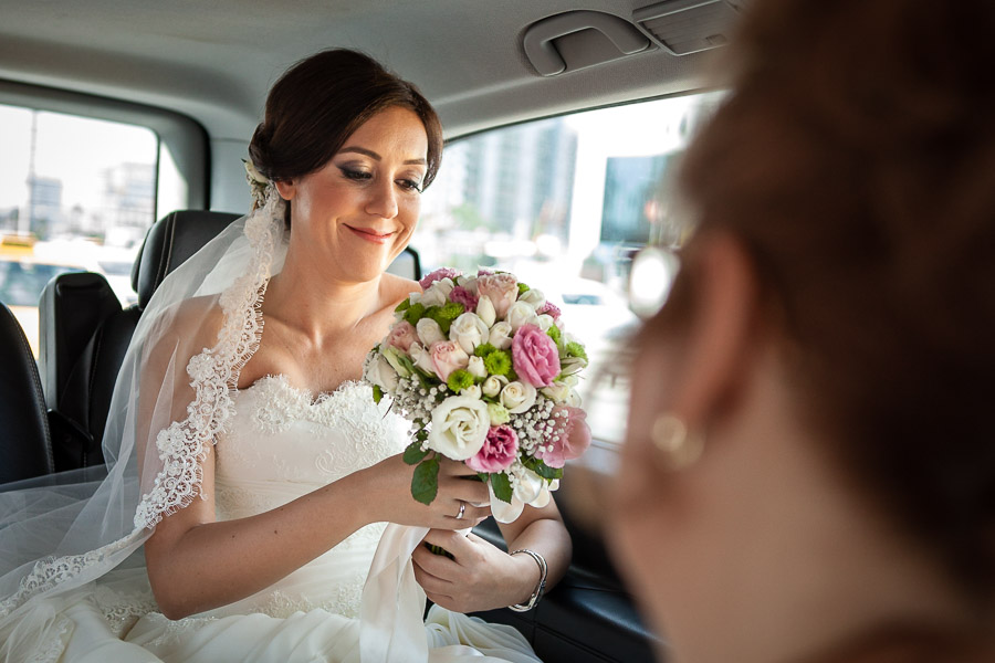 bride cgeking her bouquet in the car
