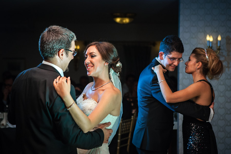 bride dancing with brother while groom dancing with sister