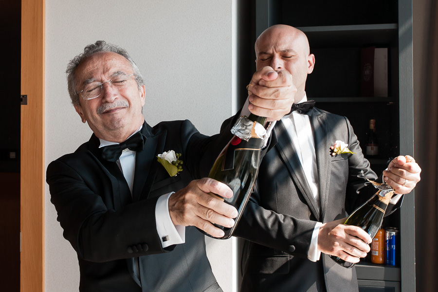 Opening a champagne at DoubleTree Hilton Moda wedding
