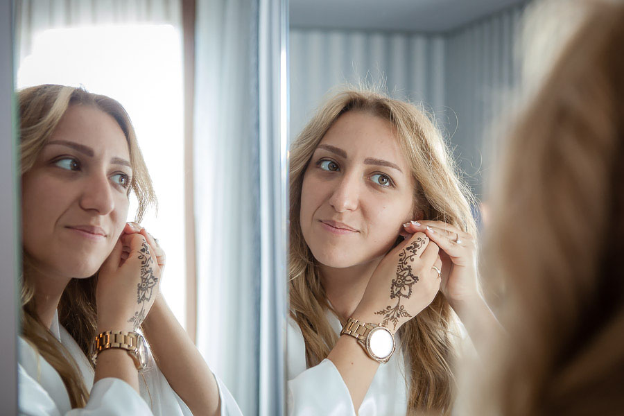 Bride putting on earing on mirror