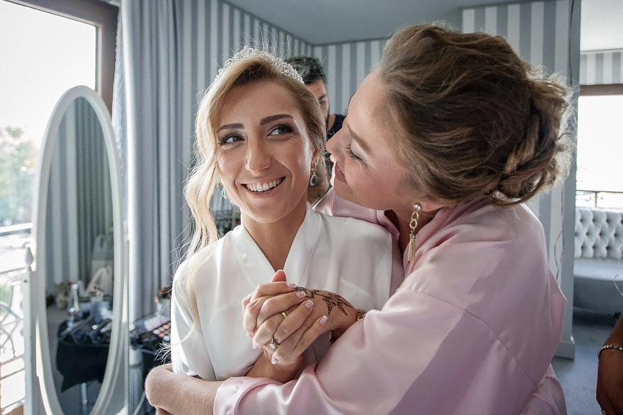 Bridesmaid hugs the bride