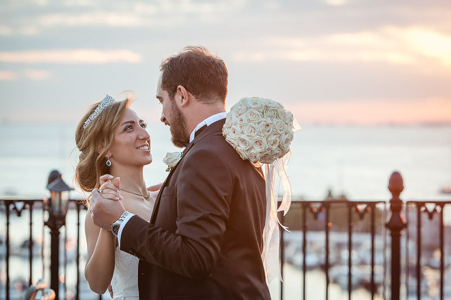 Bride and groom dance on rooftop against sea view