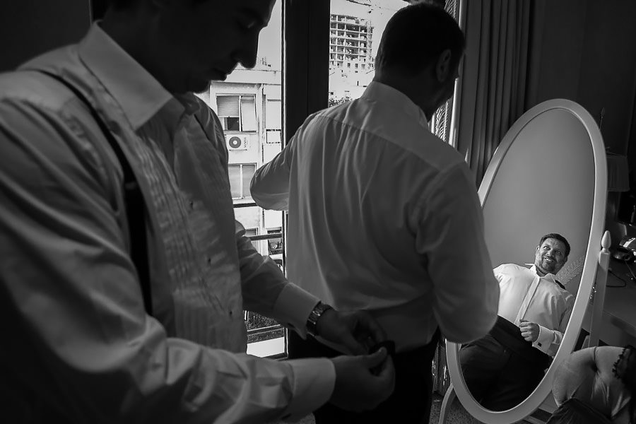 groom checking himself in the mirror