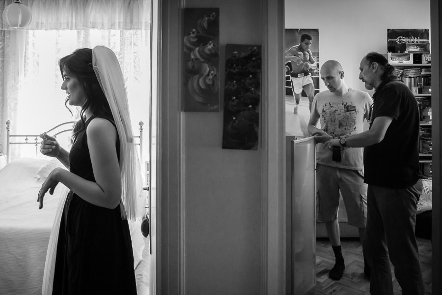Bride getting ready in one room while groom and father in other room
